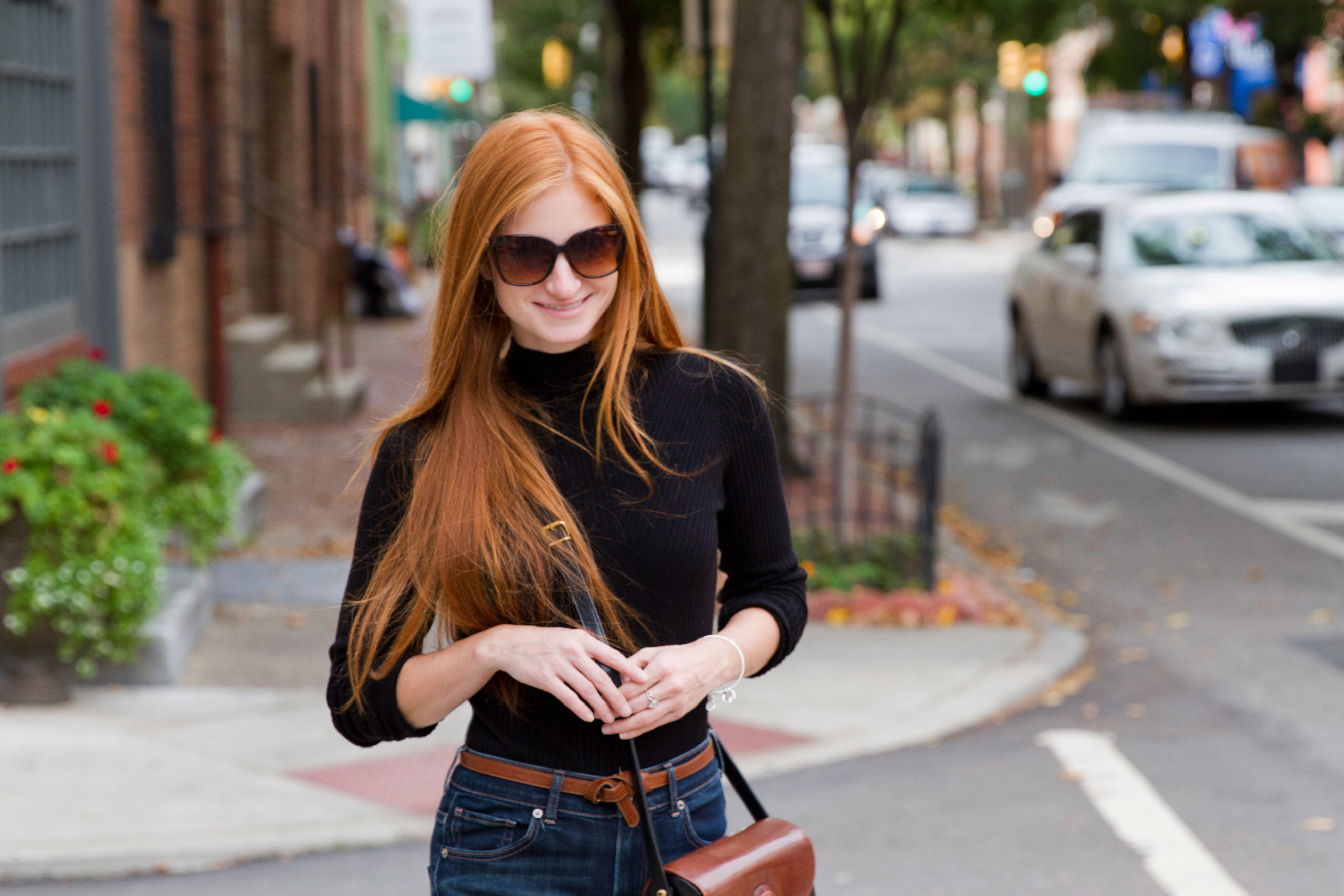 redhead girl smiling while walking in black shirt