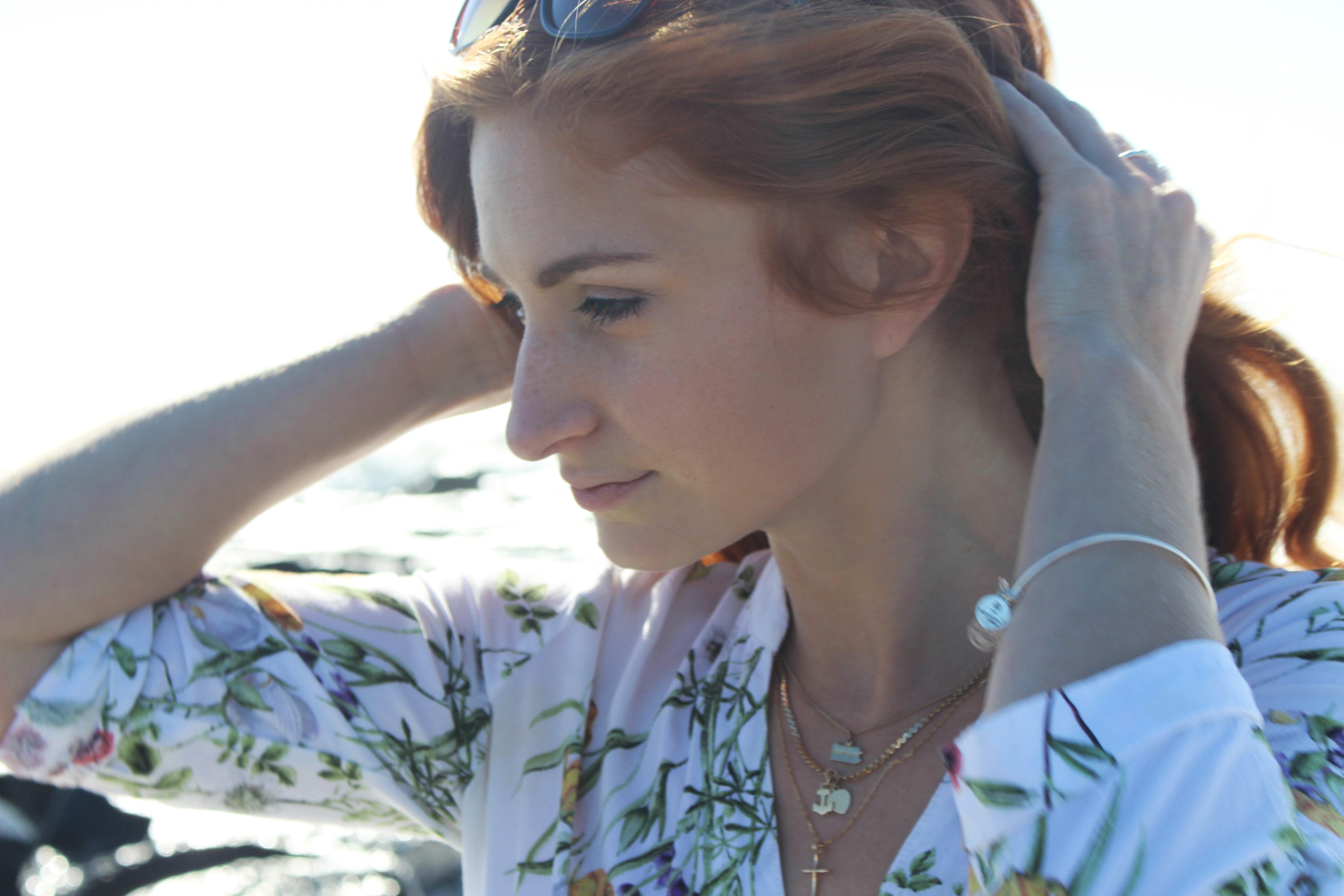 Redhead Girl pulling hair back wearing jewelry