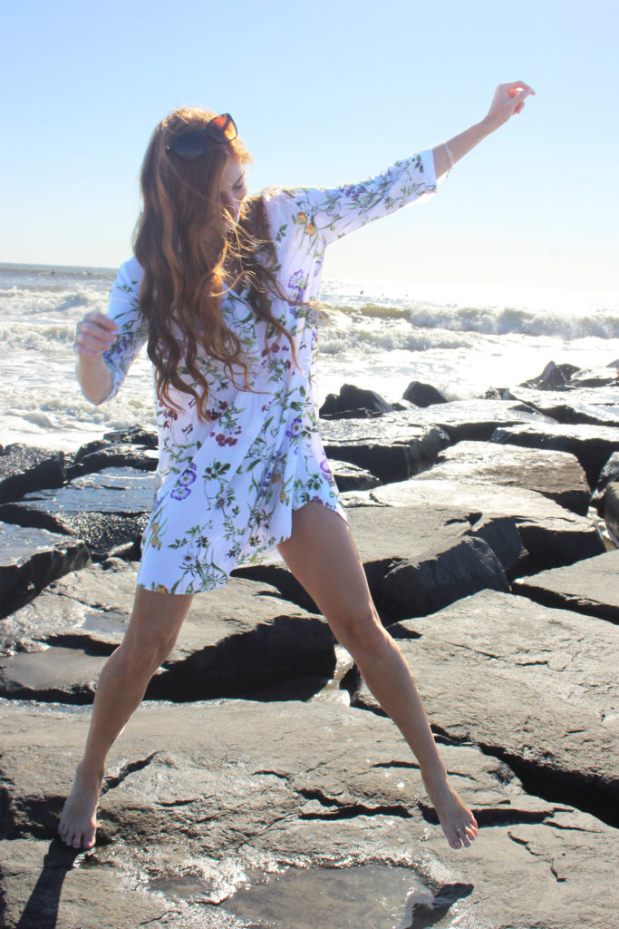 Redhead jumping on rocks at beach wearing floral dress