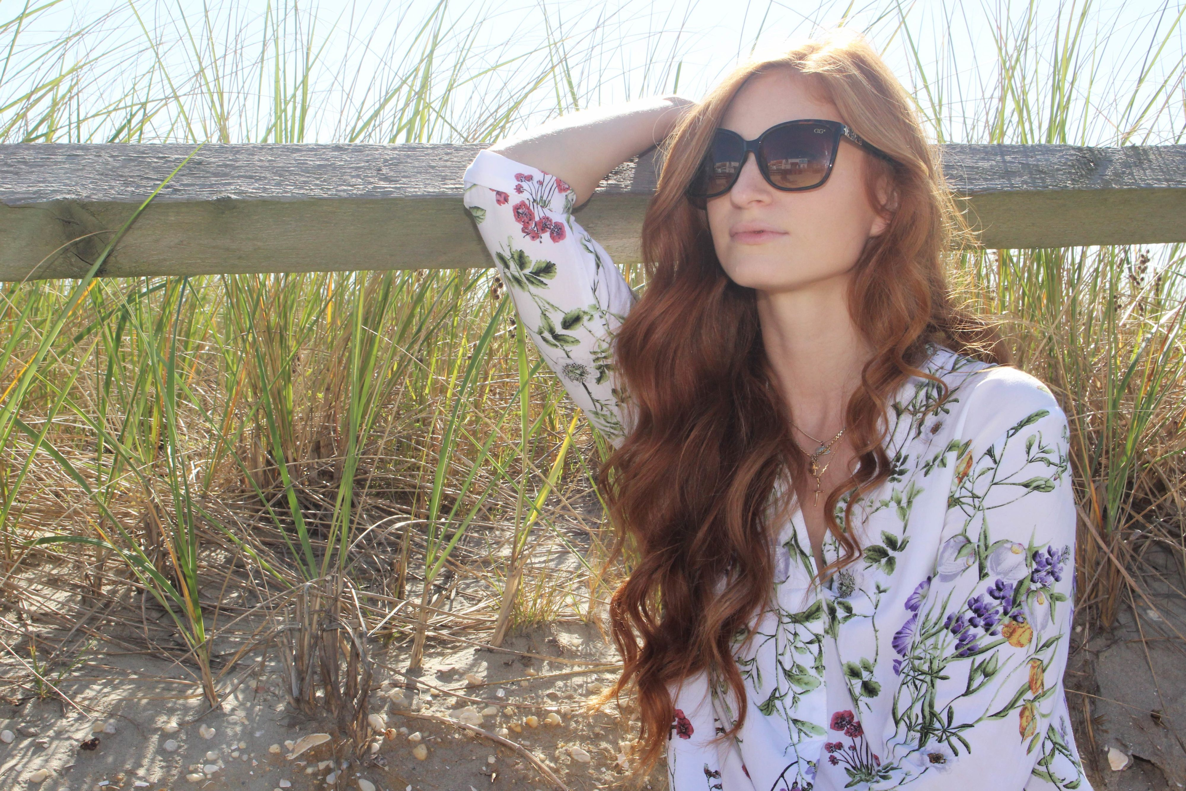 Redhead leaning on fense at beach in floral dress and sunglasses