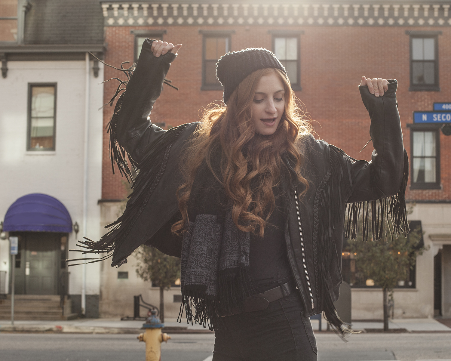 redhead girl with arms up in fringe leather jacket