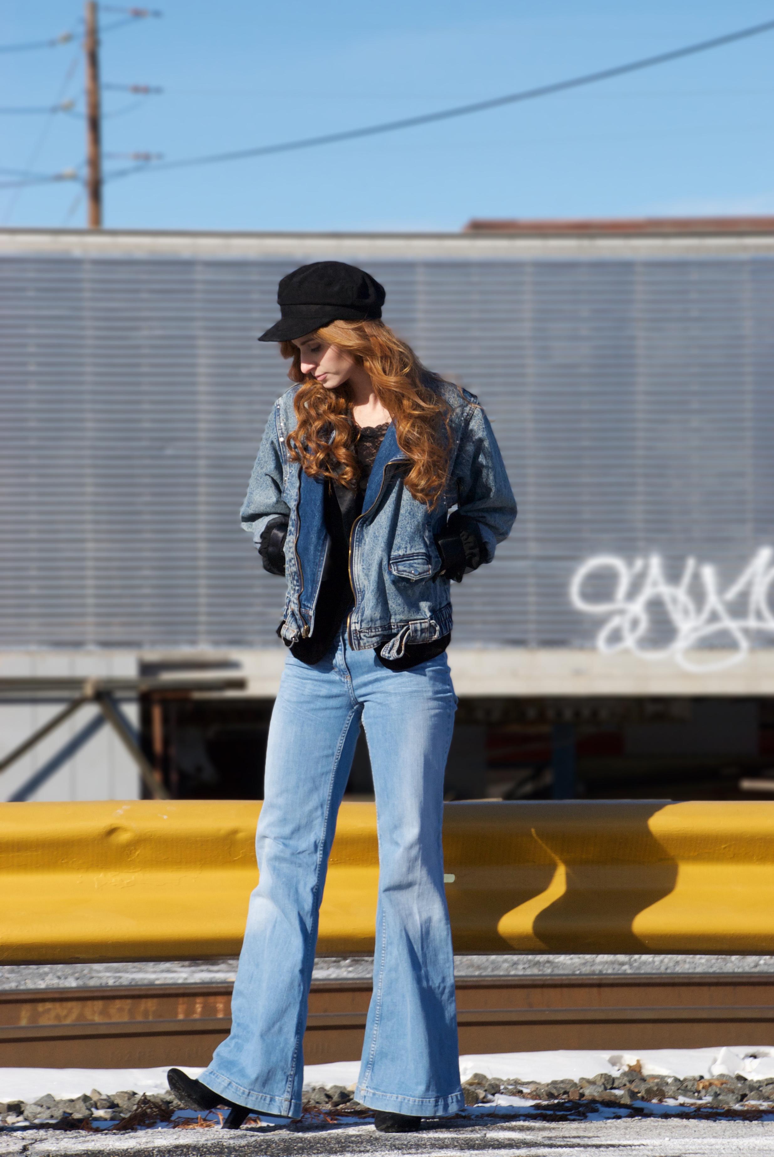 Redhead girl dressed in denim by traintracks looking down