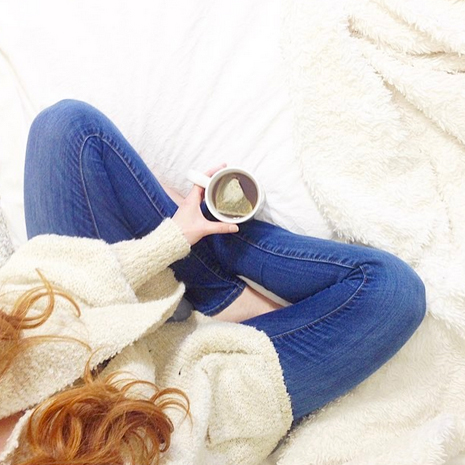 Redhead girl with cup of hot tea sitting on bed