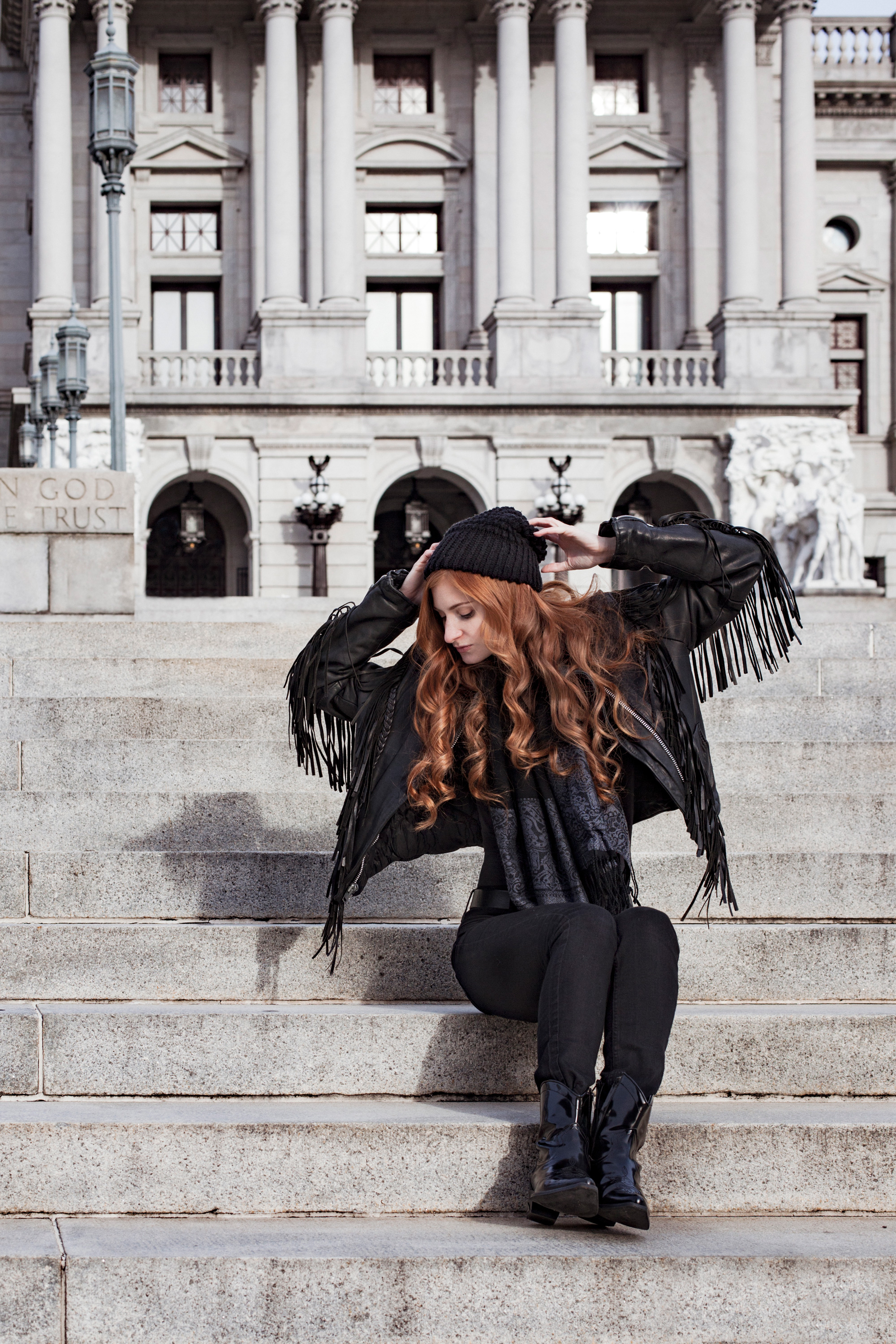 Redhead in leather jacket looking down on steps