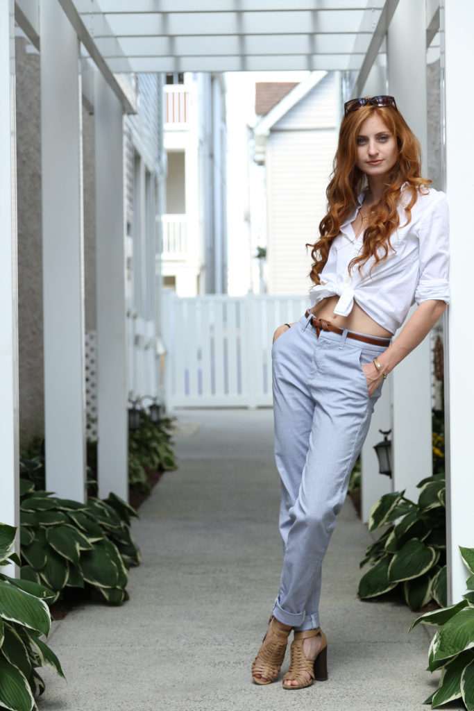 Redhead girl leaning in white shirt and blue pants