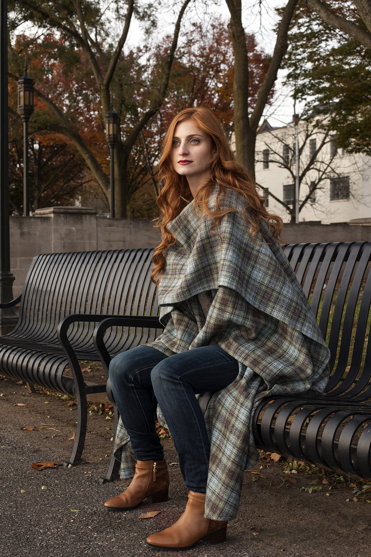 redhead girl sitting in blue and green poncho looking out