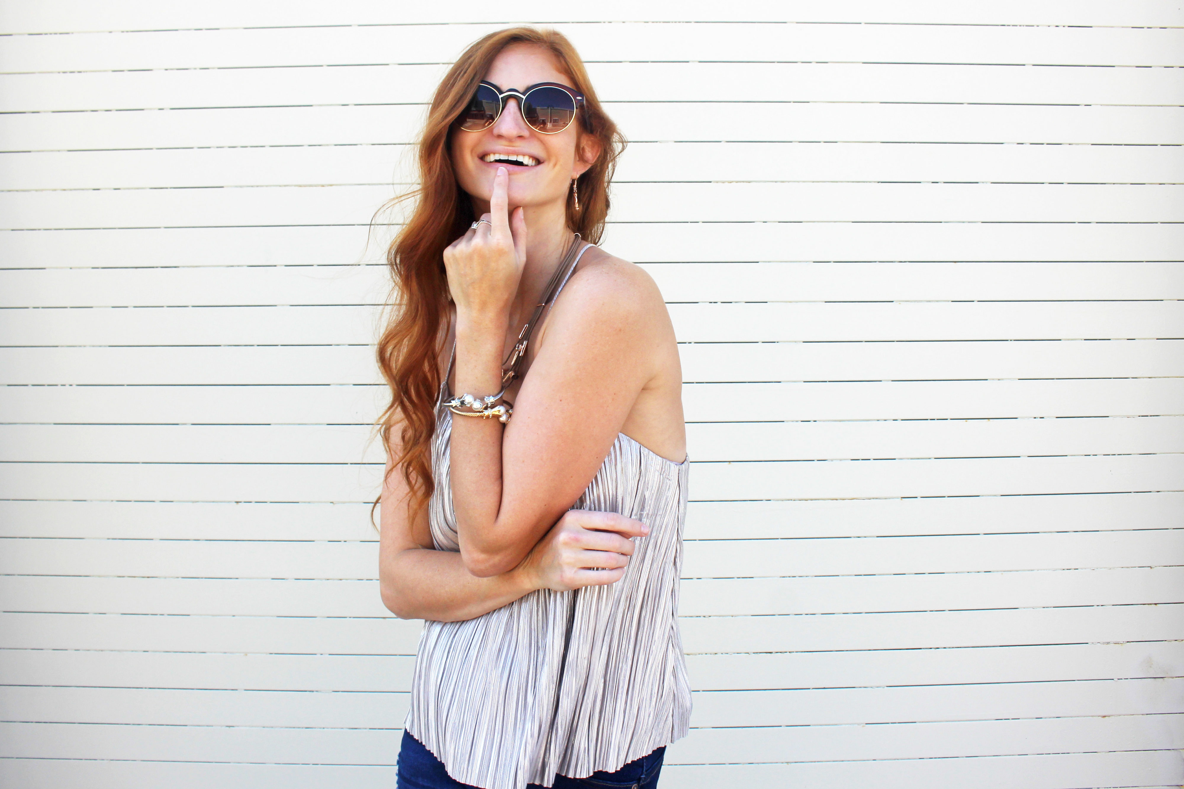 Redhead girl with finger on face smiling at camera
