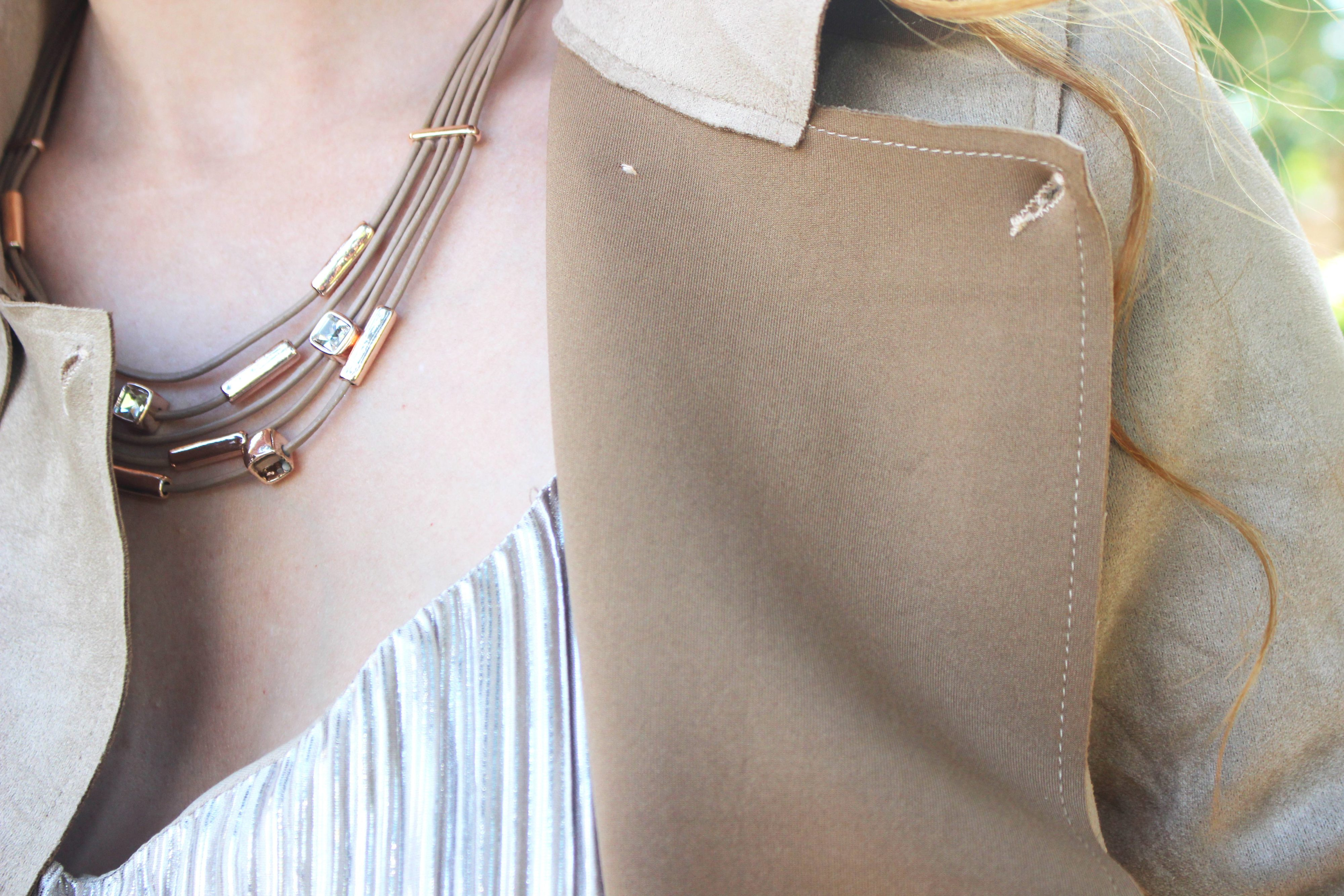 Detail photo of necklace and tan jacket