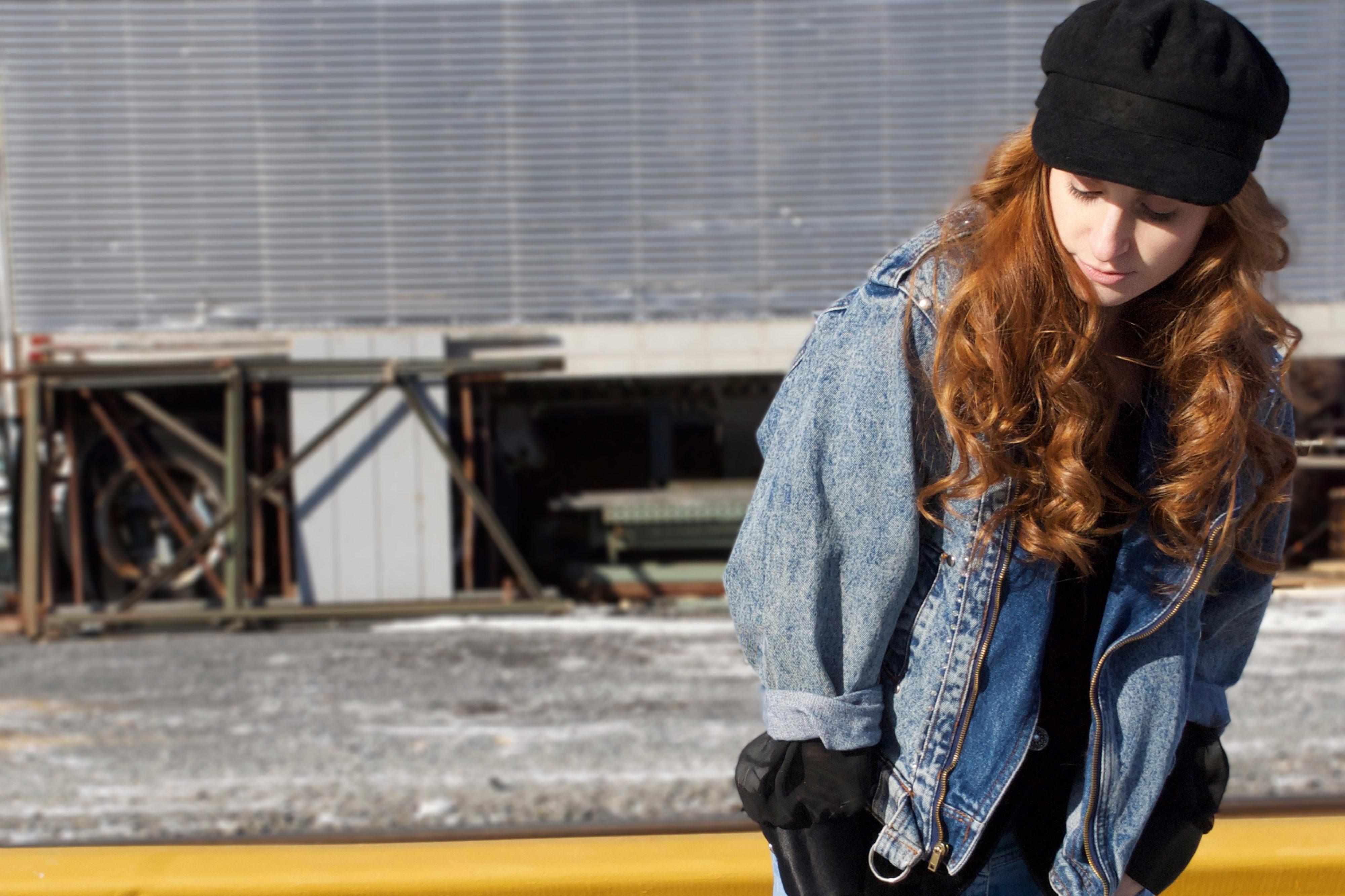 Redhead girl in denim by traintracks looking down