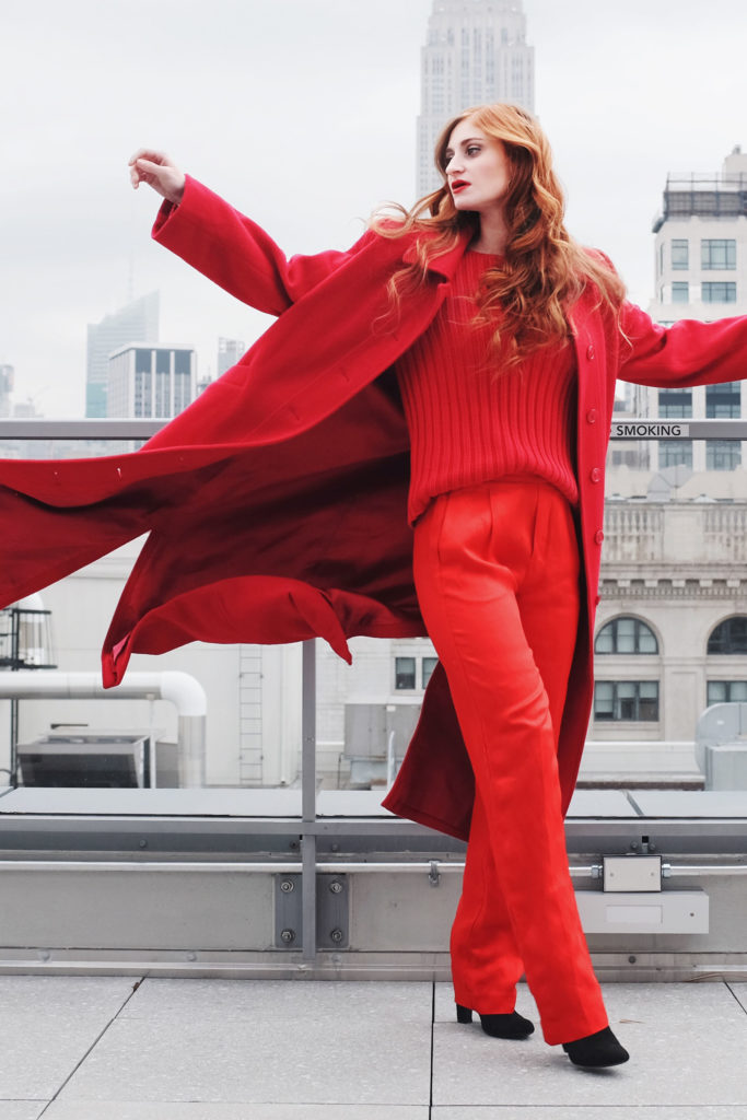 Girl in all red with skyline and coat flowing in breeze