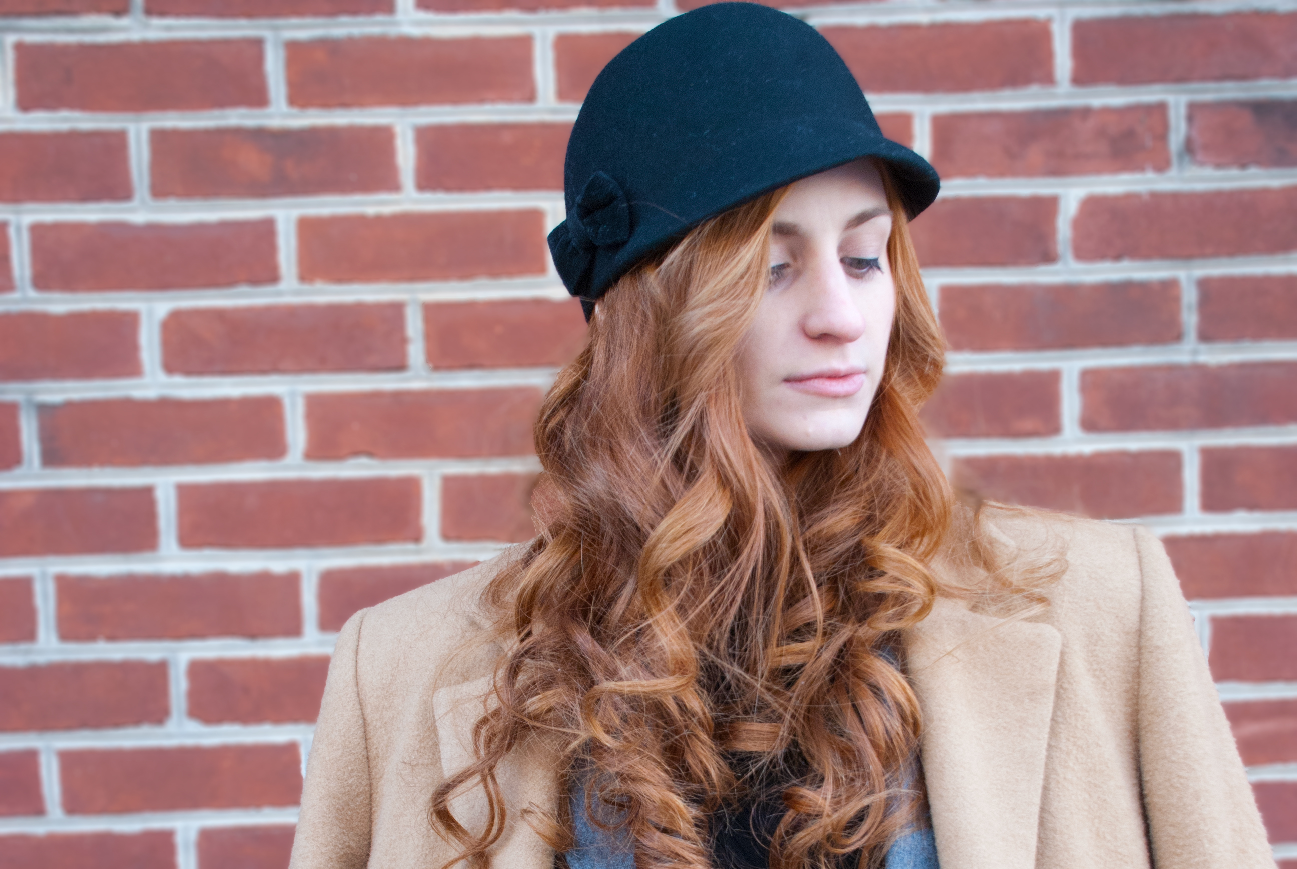Redhead girl wearing black hat standing in front of a red brick wall