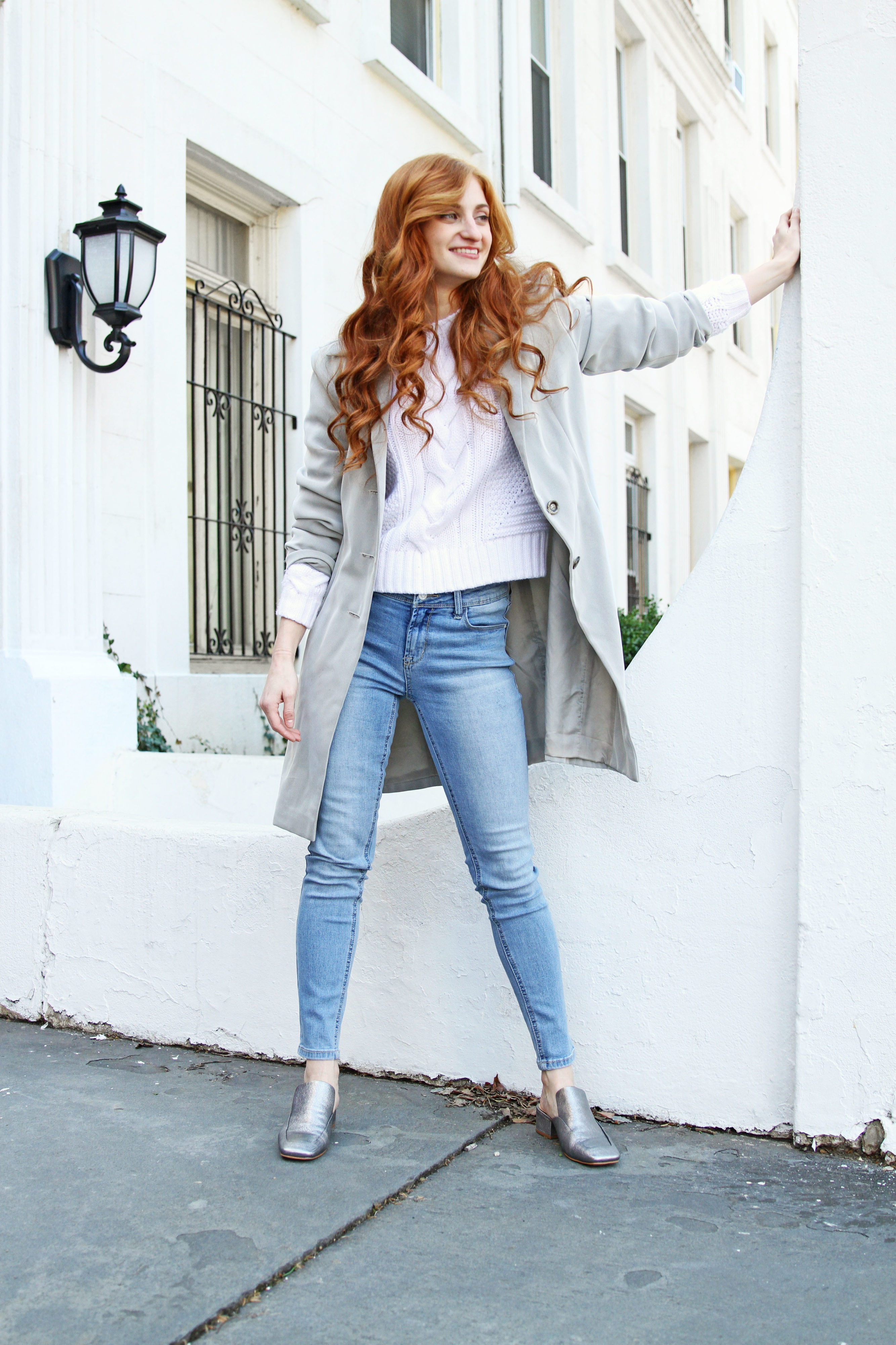 Erin Leigh Shes Red Haute Standing against white wall with sweater and jeans
