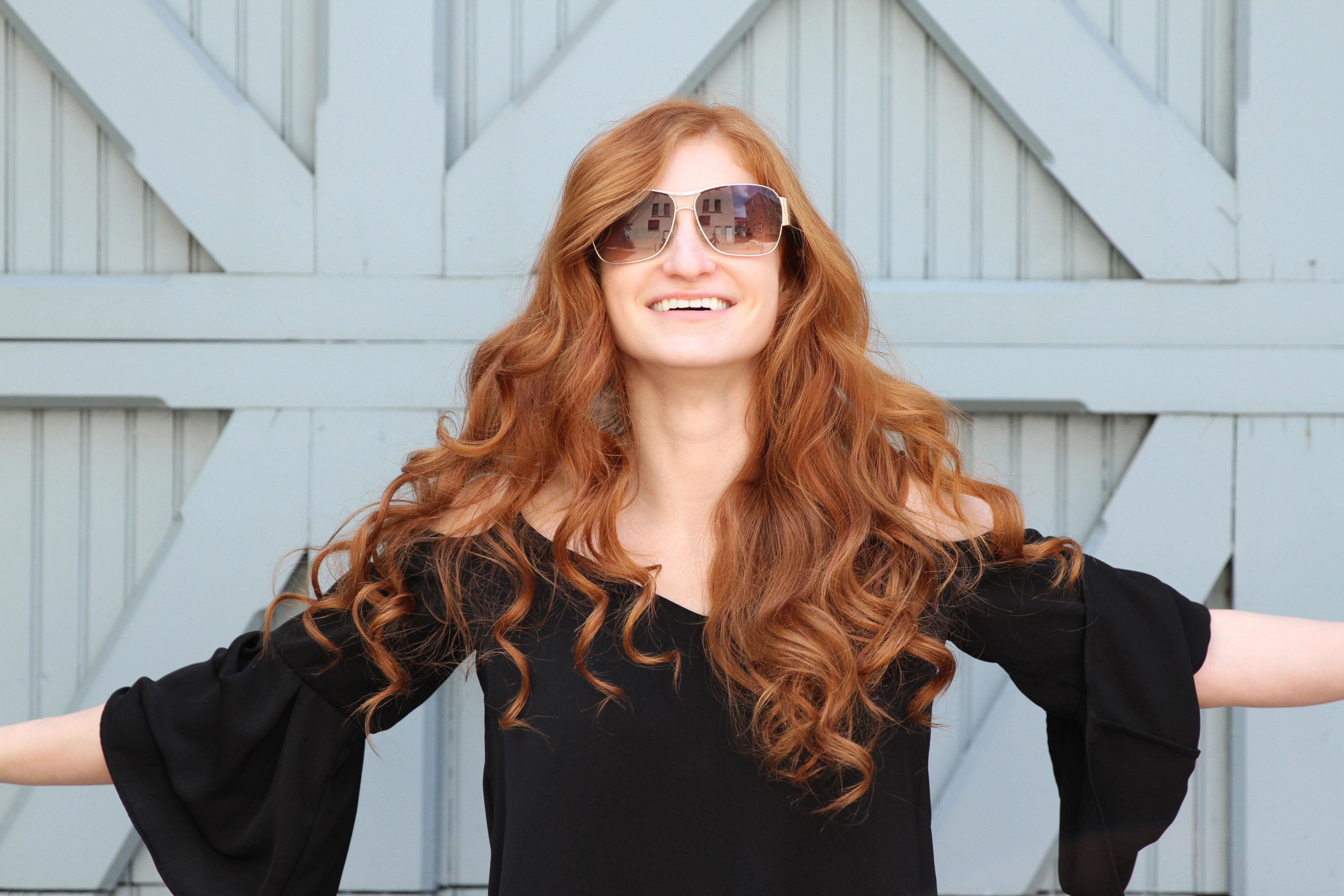 Erin Leigh She's Red Haute Redhead laid back in all black shirt with arms out