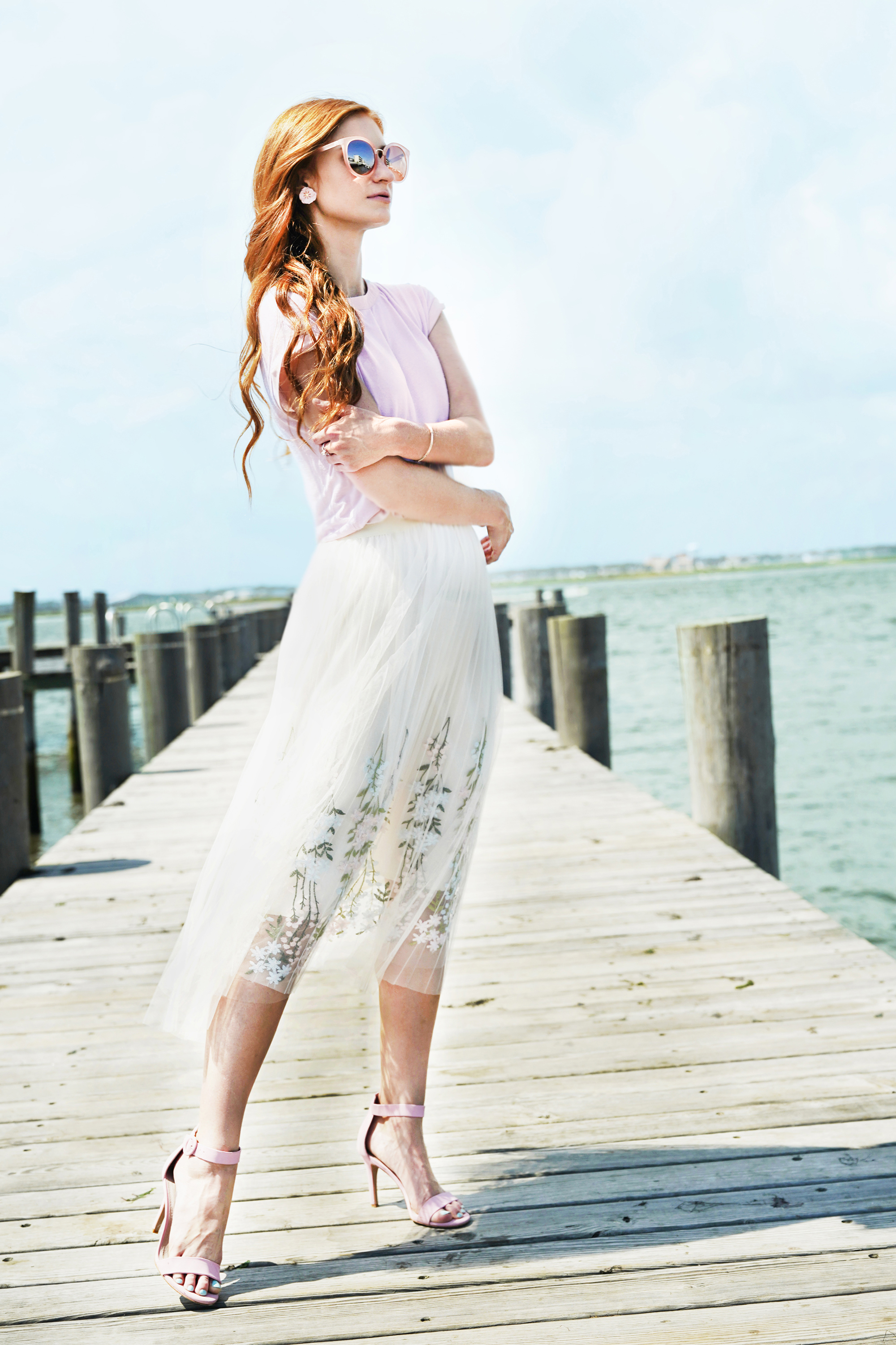 Erin Leigh She's red haute Romantic look hint floral standing on a dock in a pink shirt and floral ivory skirt