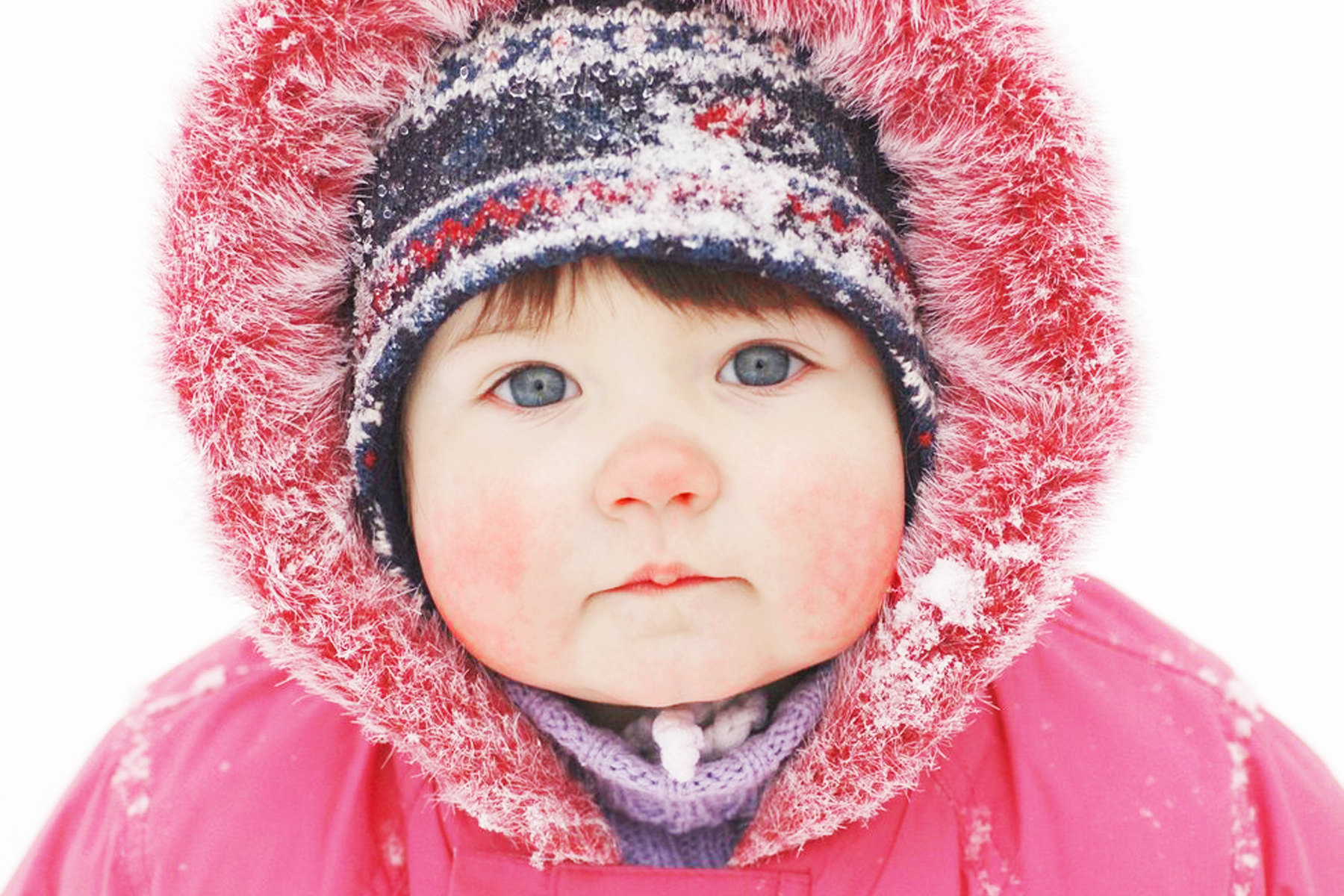 Baby with red face from cold and snow