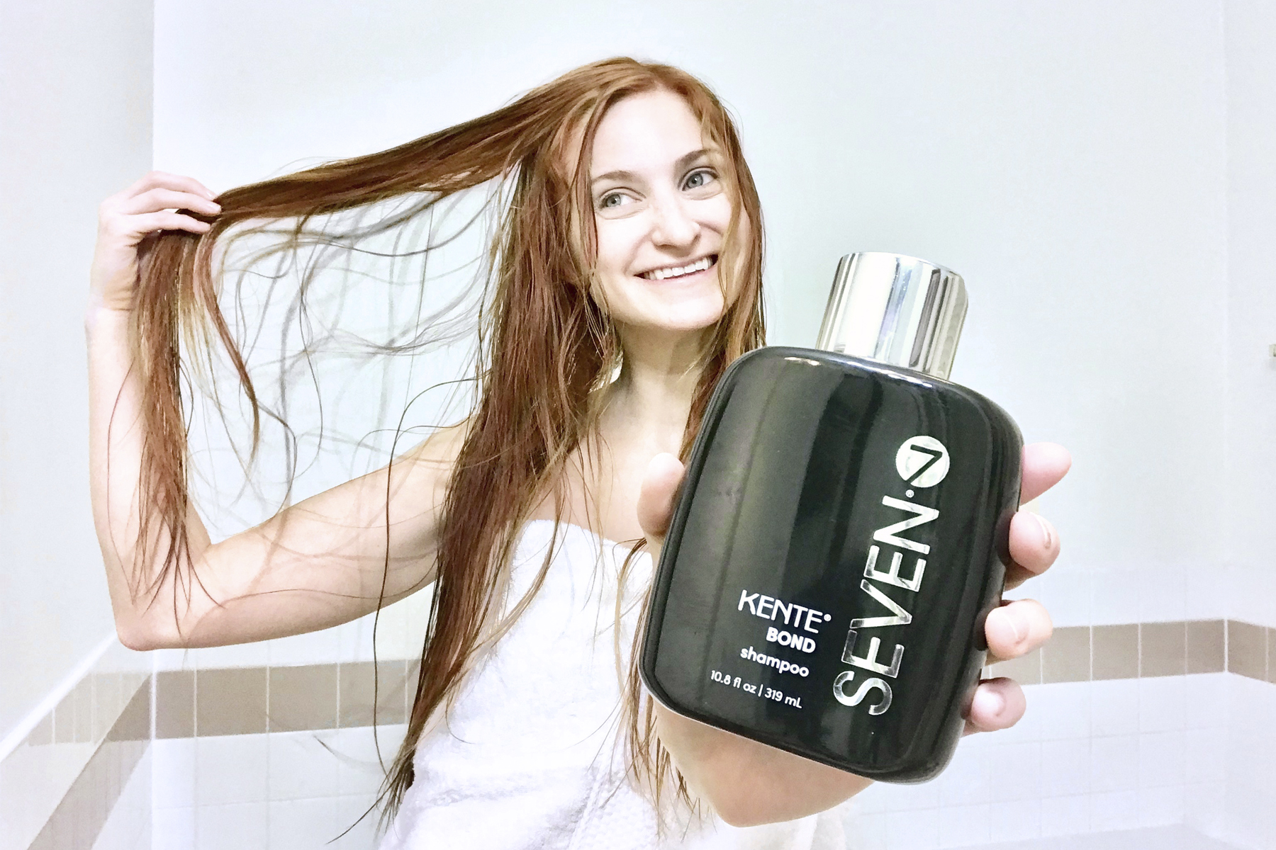 Erin Leigh of She's Red Haute holding Seven Hair Care's Kente Bond Shampoo and playing with red hair