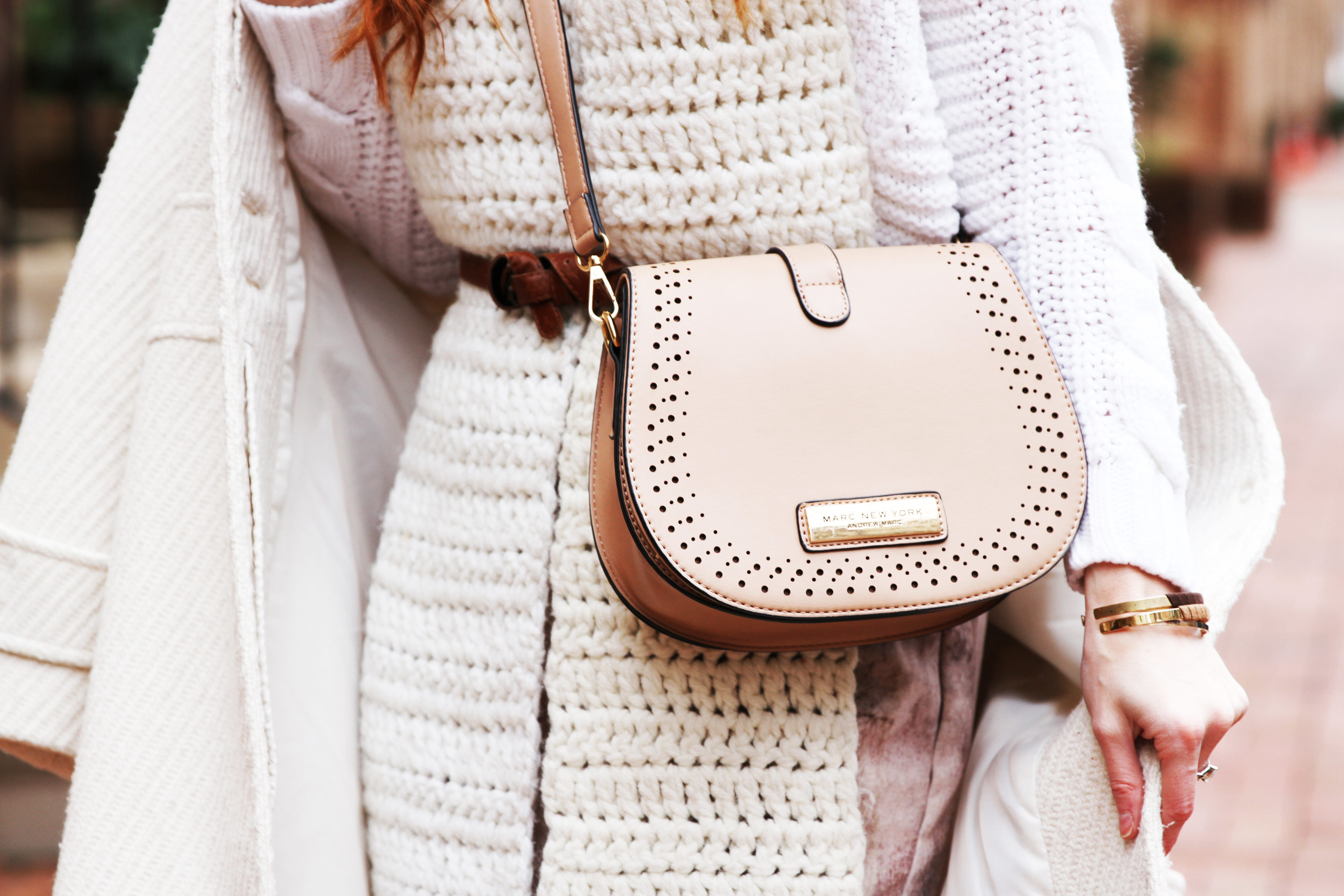 Erin Leigh of She's Red Haute wearing a white sweater with a cream scarf, marc new york bag