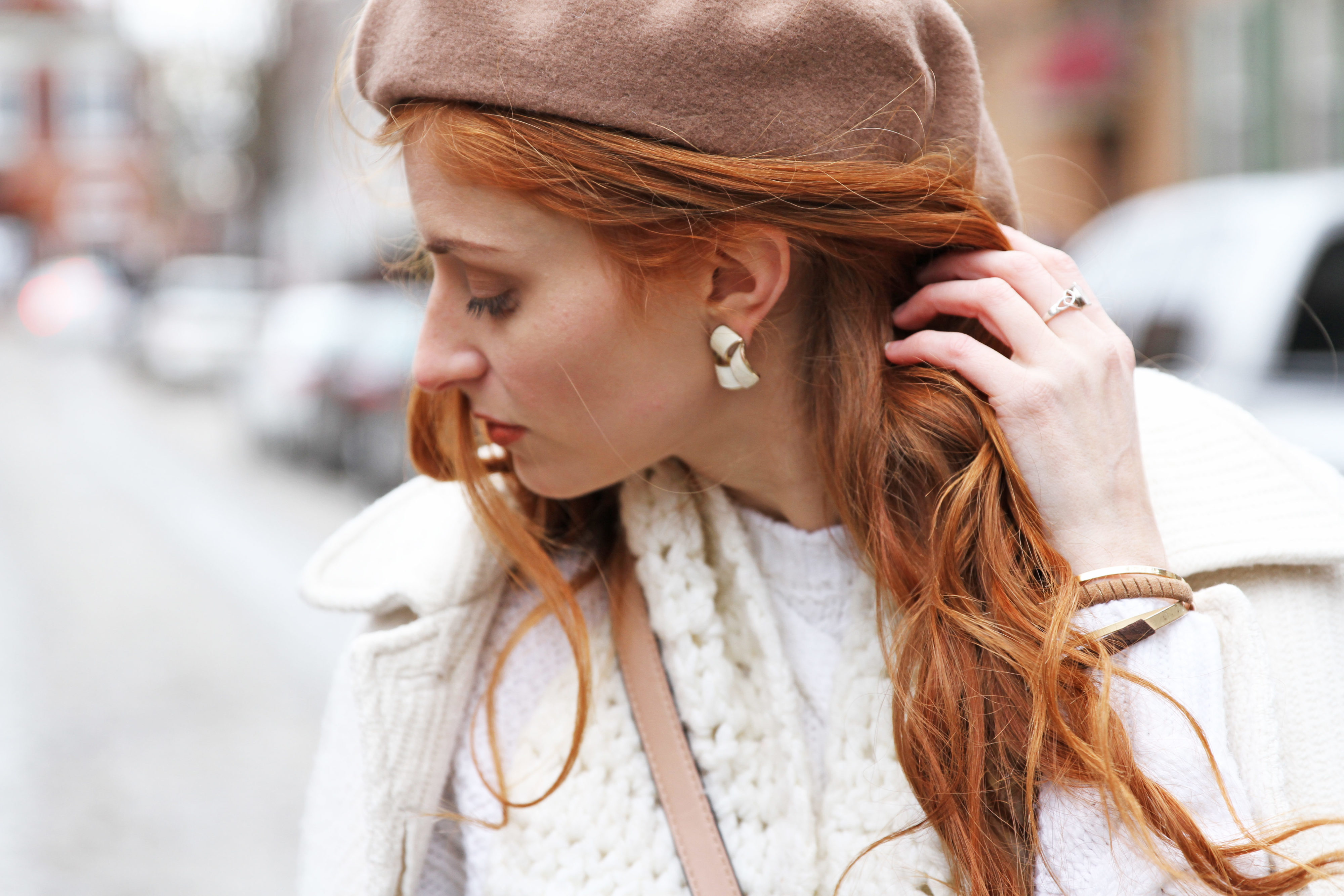 Erin Leigh of She's Red Haute pulling back red hair to show earring
