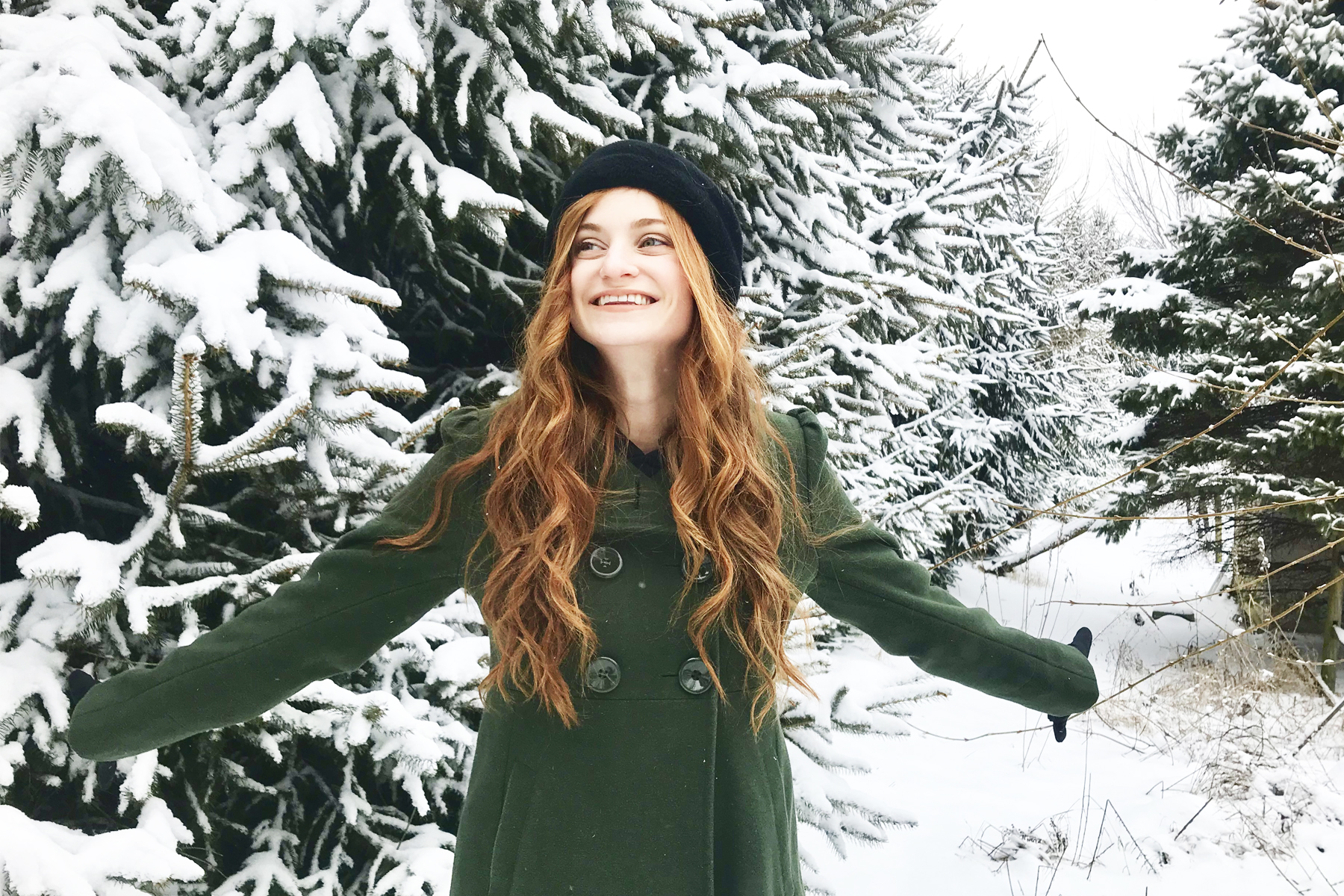 Erin Leigh of She's Red Haute standing in snow wearing green coat