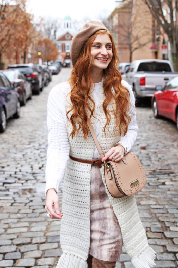 Erin Leigh of She's Red Haute wearing a white sweater with a cream scarf walking down a brick road
