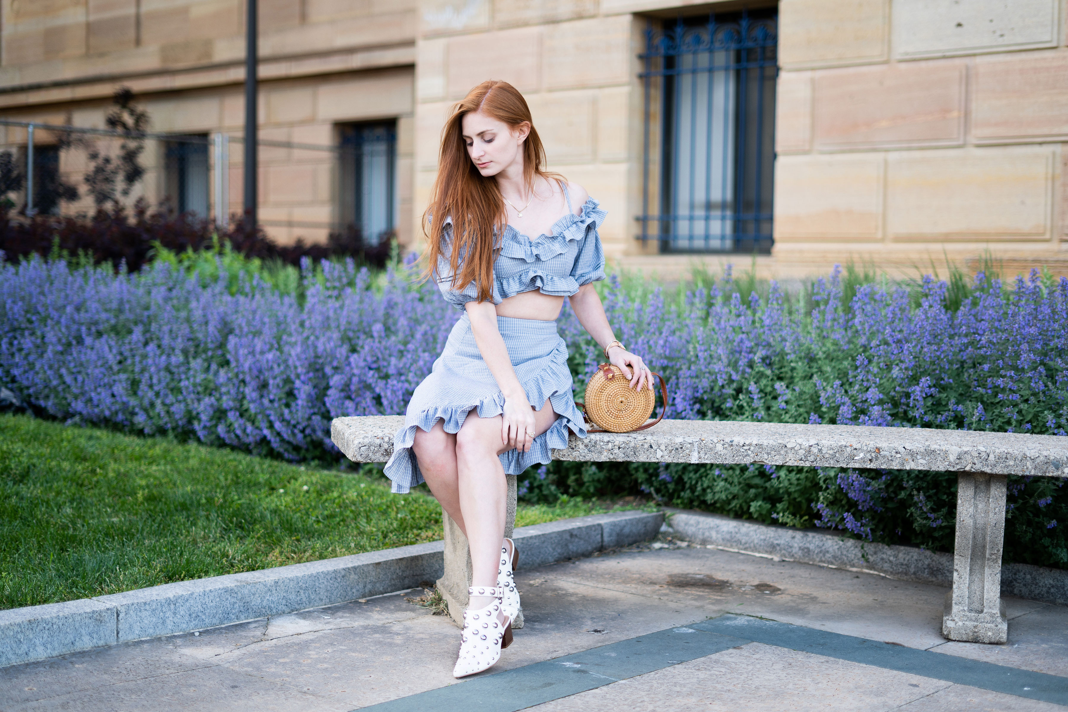 Ruffles, Erin Leigh of She's Red Haute redhead wearing blue ruffle outfit and rattan circle bag sitting in front of purple flowers redhead