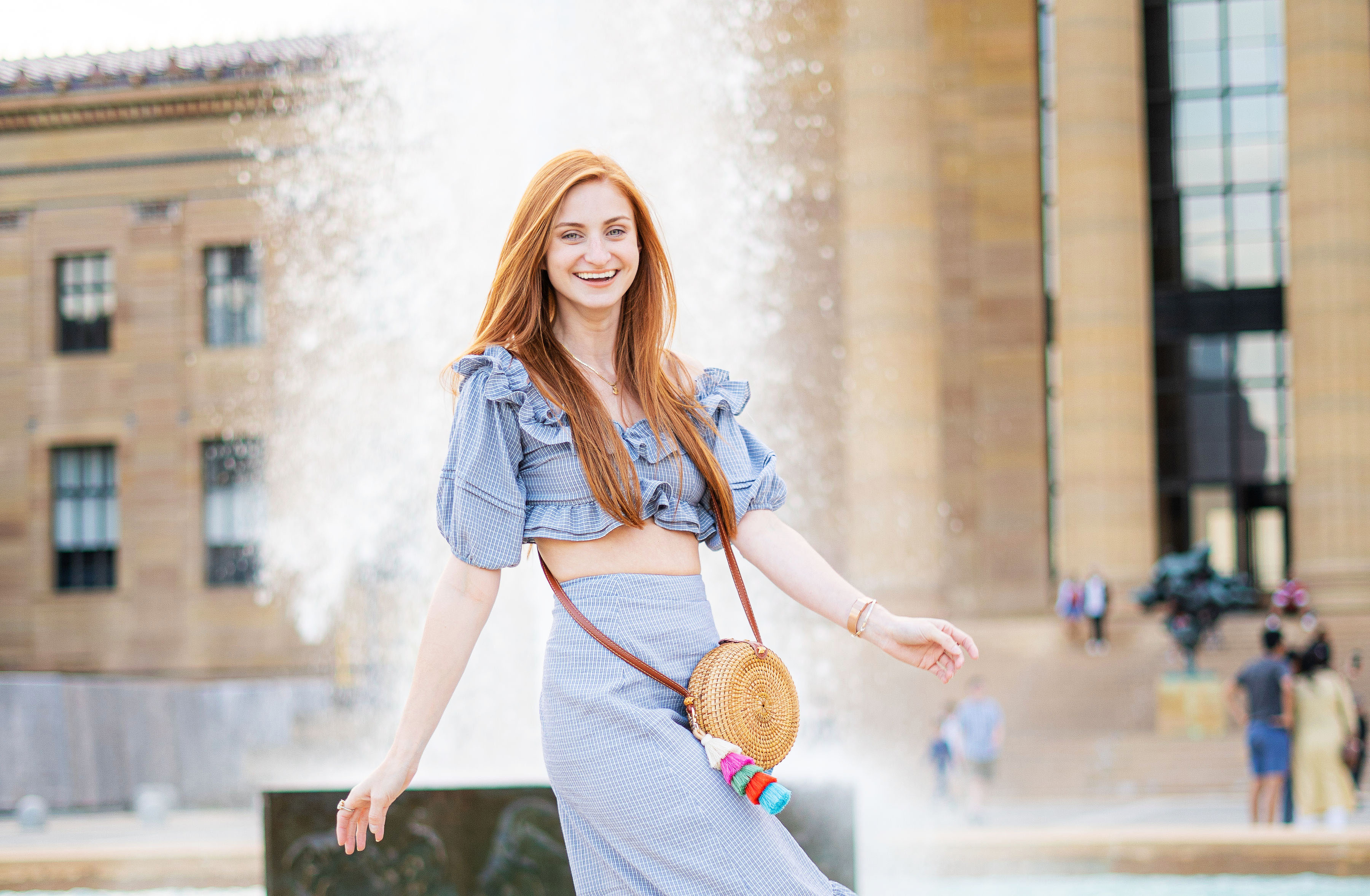 Ruffles, Erin Leigh of She's Red Haute redhead smiling and wearing blue ruffle outfit in front of water fountain with brown circle bag