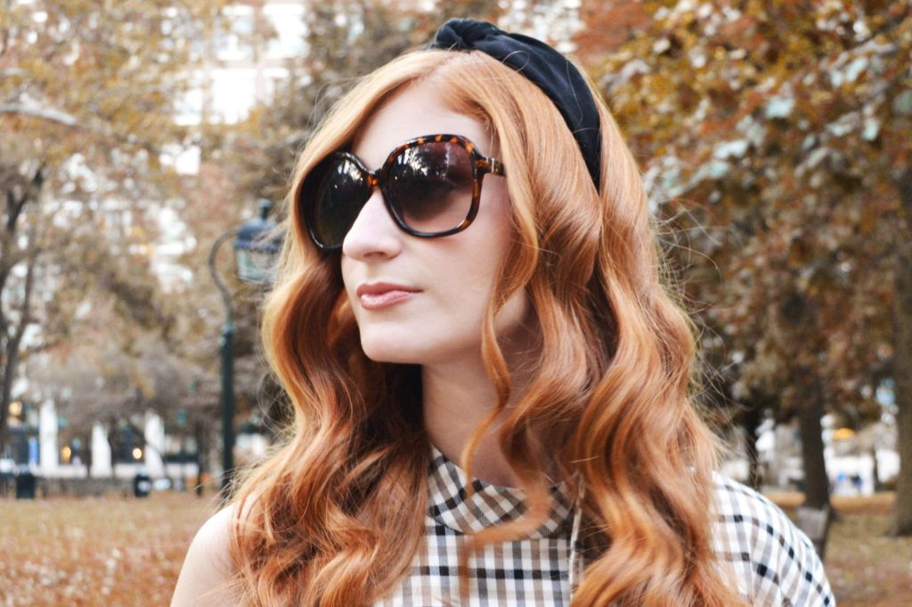 Redhead in the park in the fall wearing plaid and sunglasses