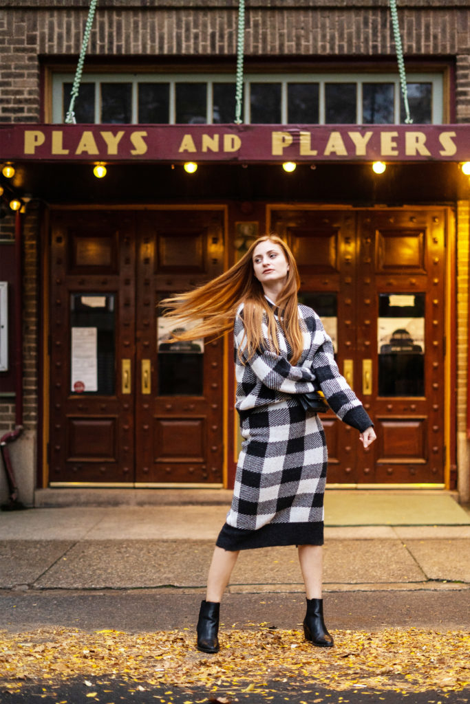Redhead Erin wearing a matching set in front of a Theatre