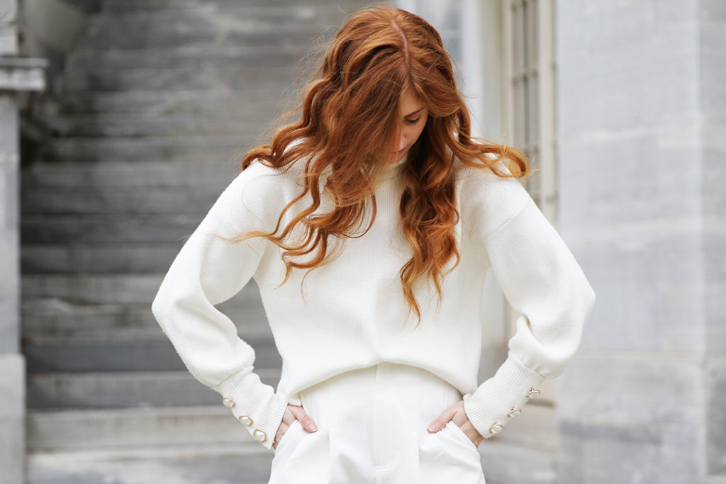 Redhead wearing all white with grey background