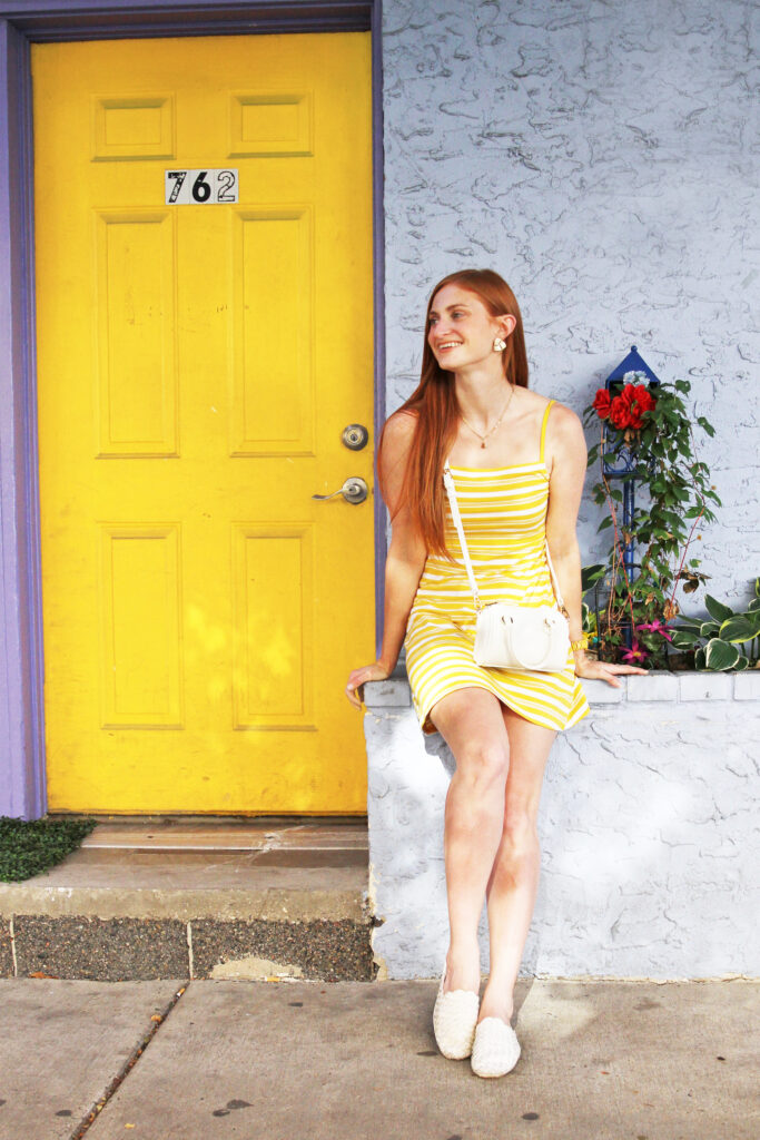 Redhead wearing yellow dress next to yellow door