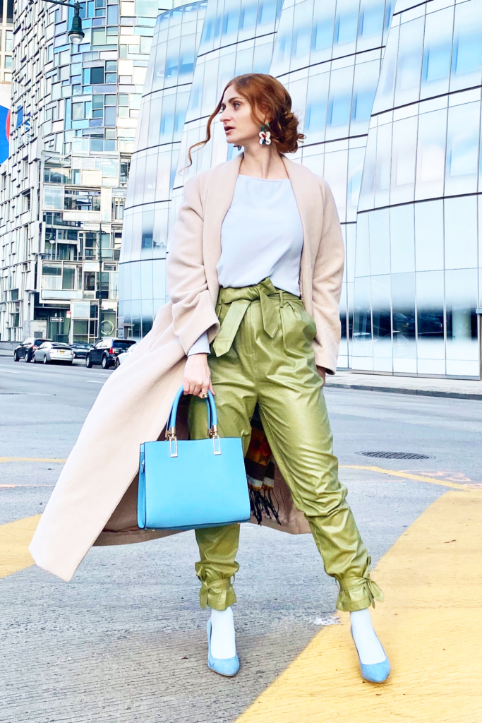 Redhead wearing green faux leather pants, a blue top, and tan coat